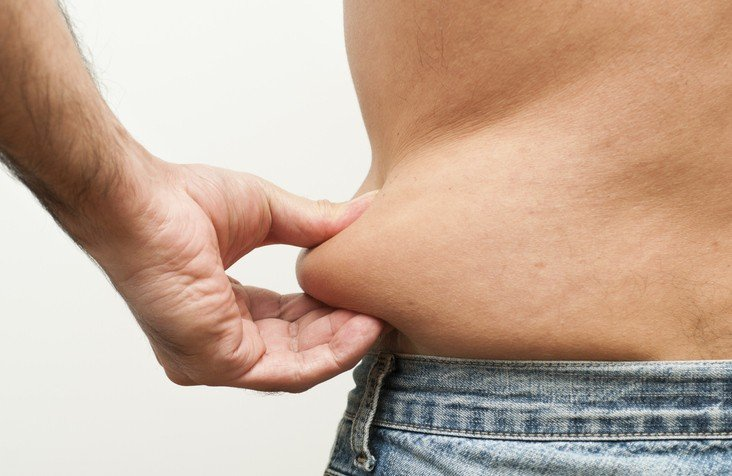A man pinches his fat from his belly area
